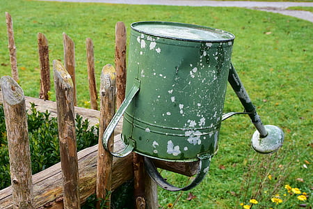 green steel watering can on brown wooden fence