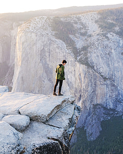 man standing on cliff on rock