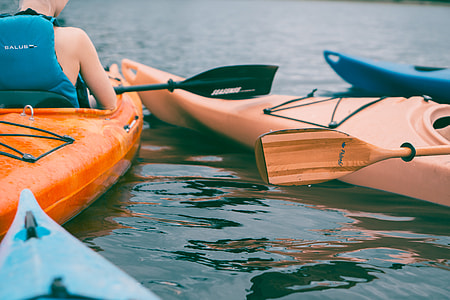 person wearing black vest riding on kayak with paddle