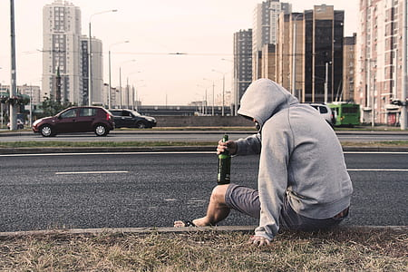 man wearing hoodie sitting beside the road holding bottle near cars during day