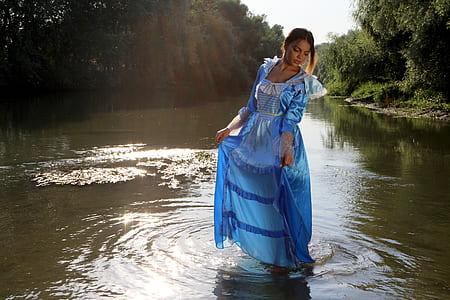 woman in blue dress standing on body of water