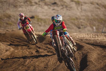 three person riding motocross dirt bike on tracks