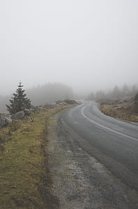 Curvy Asphalt Road Through Fog Covered Mountaion