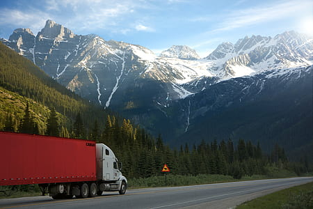 white and red trailer truck running on open road with snow-capped mountains background during daytime