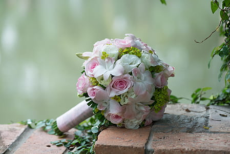 white and pink flower bouquet on brown paver brick