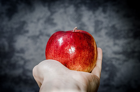 red apple on person's palm with gray background