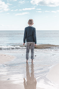 boy wearing black sweater on sea shore