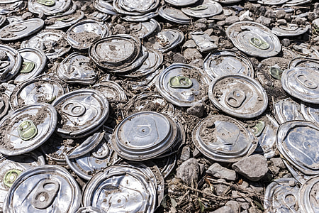 grey flat soda cans with rocks during daytime