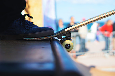 A man's foot rests on his skateboard