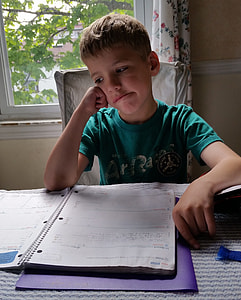 boy wearing green shirt sitting in front of table and spiral notebook