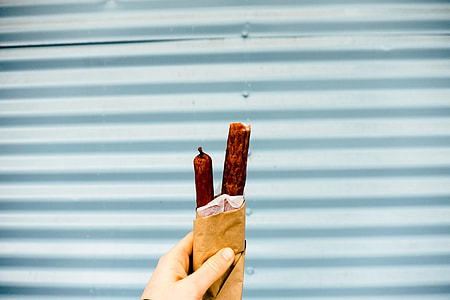 person holding paper bag with hotdogs