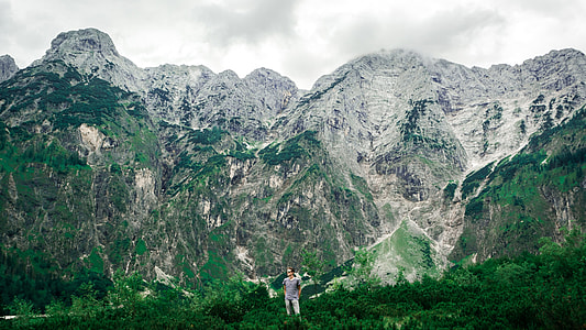 man standing on green grass with mountain in background