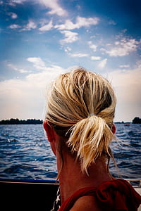 Person's Blonde Hair Looking at Body of Water