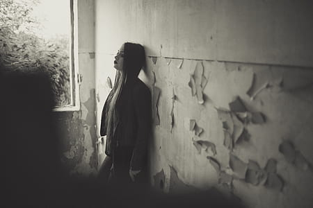 greyscale photo of woman leaning on wall during daytime