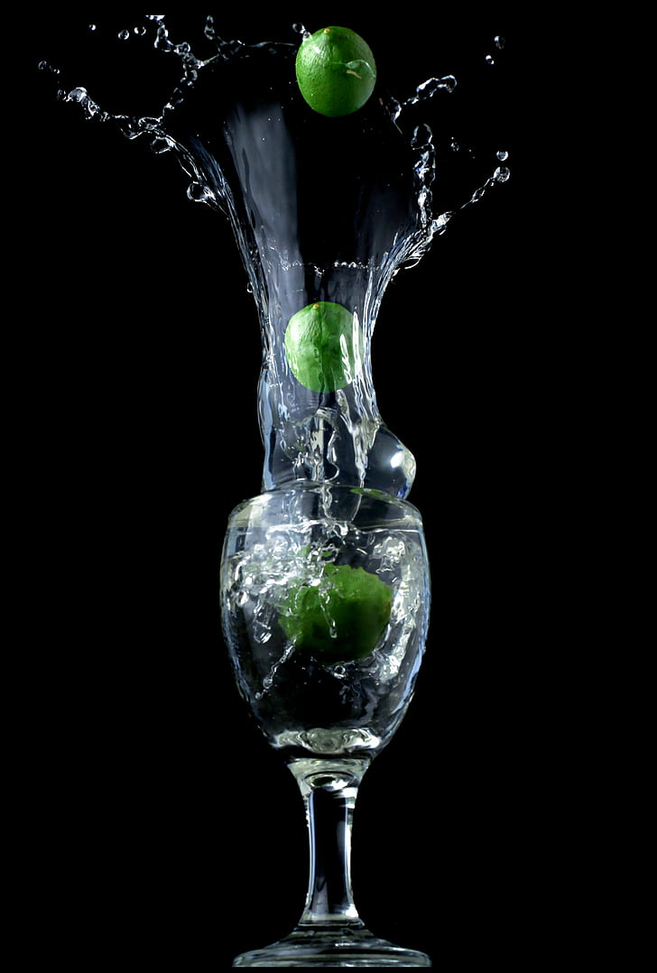 clear wine glass with three green limes