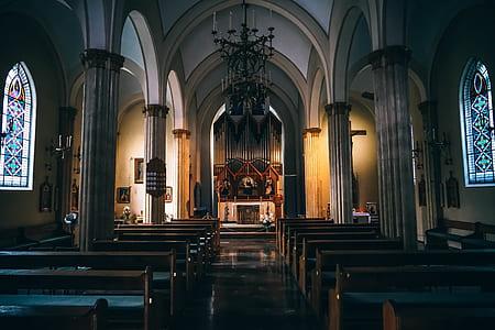 Church Pews Near Concrete Pillars in Church