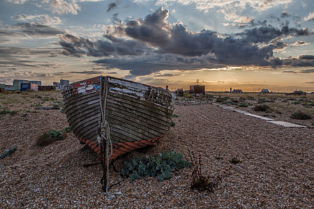 Wide angle landscape shot of an old fishing boat on the beach at sunset in Dungeness in Kent, England. Image captured with a Canon DSLR