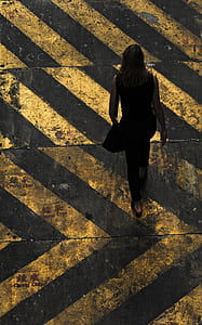 aerial view photography of woman walking on pedestrian lane