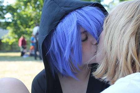 two female cosplayer kissing wearing black hoodie
