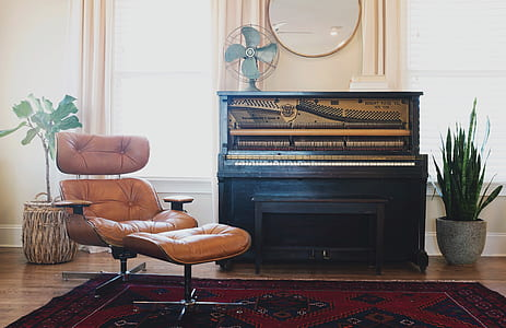 brown leather padded glider chair beside black wooden upright piano
