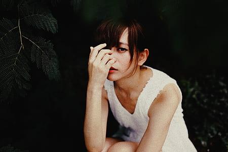 woman in white sleeveless scoop-neck shirt sitting
