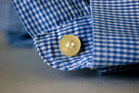 brown button on blue and white plaid textile photo
