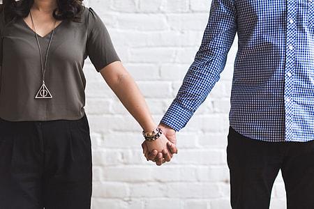 woman wearing gray shirt holding man's hand