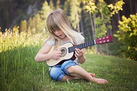 girl playing of beige guitar