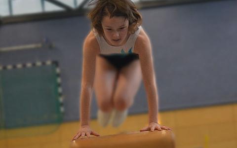 woman jumping on balance beam