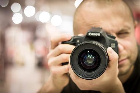 shallow focus photography of man holding DSLR camera