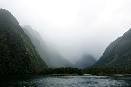 body of the water surrounded by green mountain and fogs