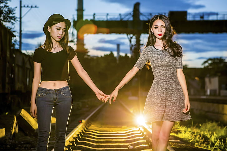 two girls holding hands on railway