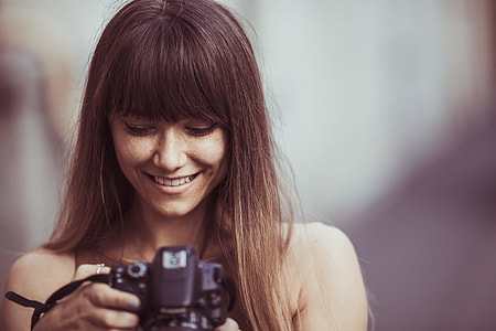 selective focus photography of woman smiling looking picture DSLR camera