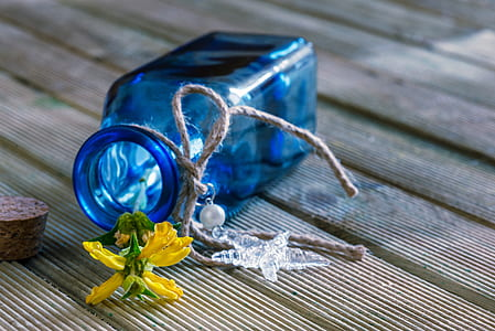 blue translucent bottle with yellow petaled flower