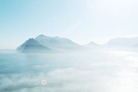 photo of highrise mountain, clouds and ocean