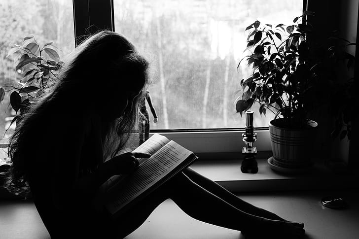 girl reading book in grayscale photography