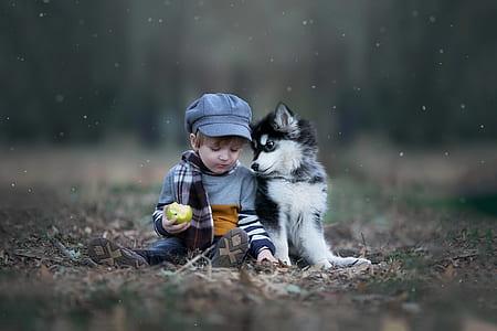 boy wearing gray sweater beside dog during daytime