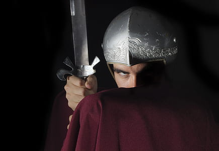 man in red cape and silver helmet holding silver sword