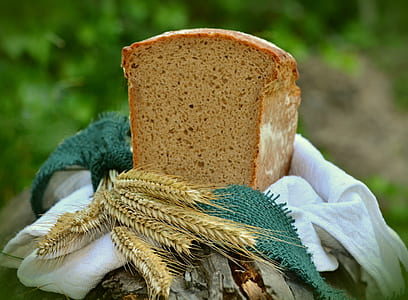 sliced banana bread on top of white textile with grains