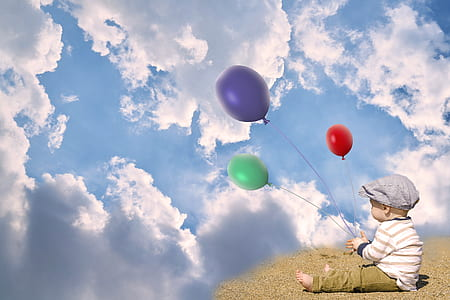 baby holding three green, purple, and red balloons