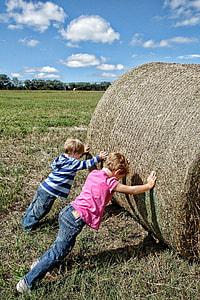 two boys pushing hay