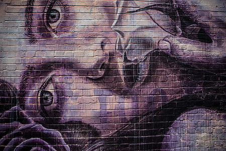 Details of purple street art applied to a brick wall in the East of London, England