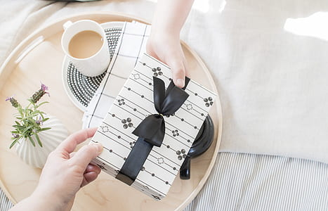 two people's hands holding white and black gift box