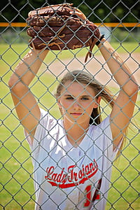 woman wearing white and red Lady Trojant button-up jersey and brown baseball mitt leaning on gray chain link fence