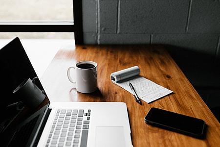 turned off MacBook near smartphone and ceramic mug on rustic table