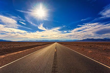 gray asphalt road between desert field during daytime