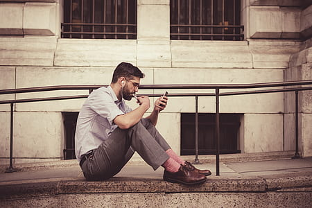 man listening to music while looking at phone
