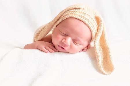 baby wearing beige rabbit beanie