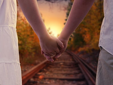 two people holding hands standing on train rail during daytime