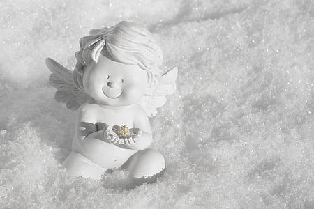 cherub white ceramic figurine sitting on the snow